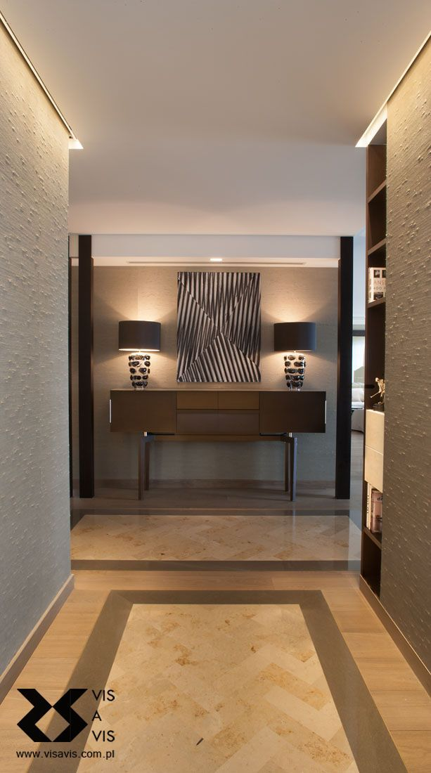 Entrance hall with a bespoke stone floor pattern. Silk wall-covering and Porta Romana table lamps