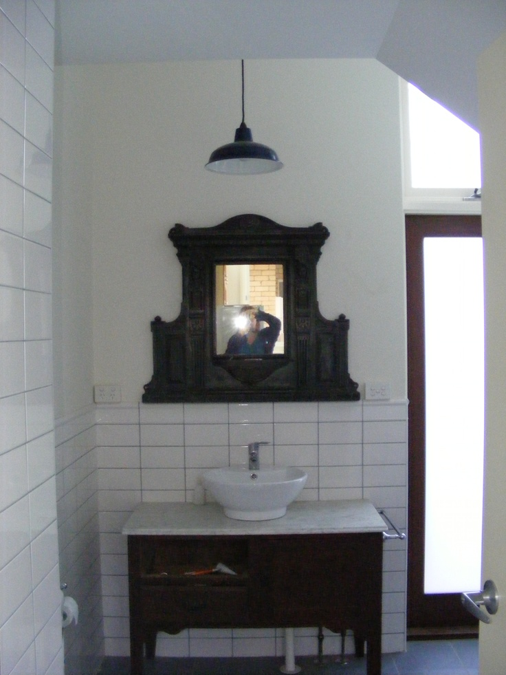 Bathroom/Laundry in original part of the house, under the staircase. I found this cheap old oak cabinet & rescued the marble top from a scrap yard. The grey grout with white tiles was inspired by European holidays and underground railway stations. I wanted an overall Victorian feel with a twist. This mirror is one of my most favorite and expensive secondhand shop finds, but it was totally worth it. The door leads to outside and the washing line.
