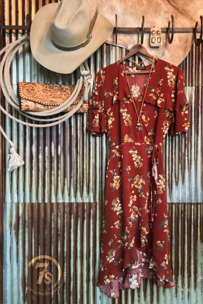 The Centralia - Rust floral wrap dress. Delicate retro floral pattern. V-neck with hidden snap closure and waist tie. Light flowy ruffle hi-lo hem. Tiered ruffle sleeve. Perfect romantic hemline and fit. Highest part of hem hits a little ways above the knee.