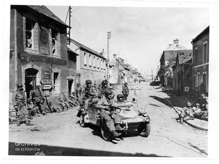 14 juin 1944 Carentan, au carrefour de la rue Holgate et de la RN 13, quatre paras de la 101e division aéroportée, à bord d'une Kübelwagen allemande, passent devant leurs camarades au repos le long de la devanture du café-restaurant Désiré Ingouf