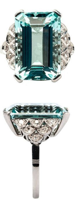 jsOp *Aquamarine and Diamond Art Deco Cocktail Ring, Valley Falls is a show-stopping late Art Deco era platinum set cocktail ring centering a stunning 10.26ct Retangular Step Cut natural aquamarine. Flanked on either side by decadent, scalloped stepped-down shoulders and studded with twelve Single Cut diamonds totaling approximately 0.12ct. Circa 1930-1940s.