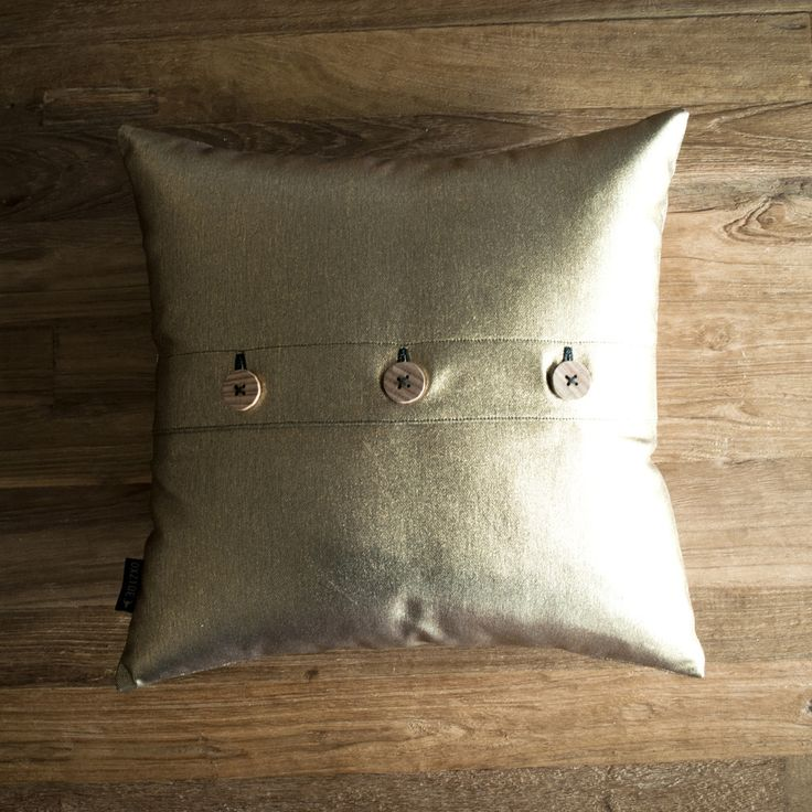 These simple cushions are made from beautiful metallic denim. Perfect cushions to make a statement on any couch, bed or chair. Cushions are finished with three handmade feature Tasmanian Oak buttons on the back. Available in Silver, Copper or Brass.Insert is included with this cushion.Product Fabric: Brass DenimSize: 40 x 40