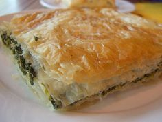 1 cup oil, preferably olive oil 1 1/2 packets (or about 30) pastry leaves (Filo Dough) 1 1/2 pounds spinach, chopped 1 cup diced feta cheese 1/2 cup chopped green onions 2 eggs salt, half teaspoon (NOTE: A medium-sized, round baking pan is recommended because it's more authentic but any medium-sized baking pan will do).