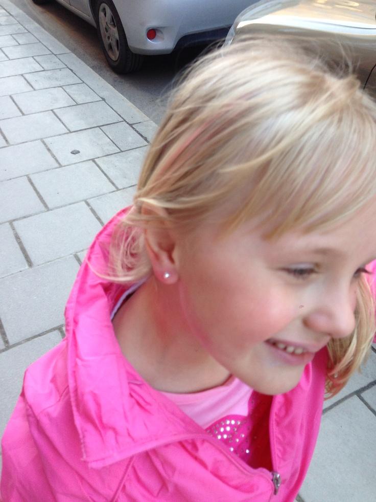 Stolt tjej med nytagna hål i öronen
