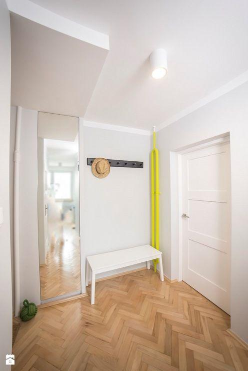 Białe ściany, sufit i drzwi. Jedyne kolorowe akcenty to czarny wieszak i jaskrawożółto pomalowana rura w kącie.