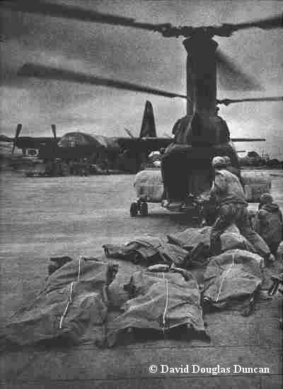 1968. Vietnam War. // Night was near when two great birds beat through the clouds to squat upon the runway - two gaping-beaked, potbellied prehistoric birds: messengers come now to carry off the fallen men of the day's battle.  Marines from Khe Sanh joining those other men killed in all otherwars.  Then they were gone and it was night. //  by David Duncan Douglas