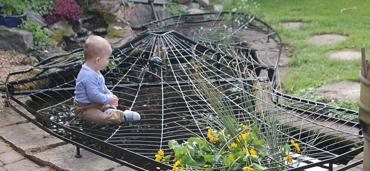 A hanging spiderweb pond cover for protecting children from the pond as well as keeping herons from the fish.