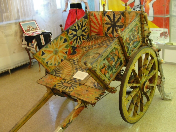 Sicilian Carts are covered with colorful folk designs and motifs that seem to be primarily medieval (Crusader knights fighting the Arabs) or religious. They may also be carved with gargoyles, mermaids, angels, & flowers. Underneath the carts, such things as the cartman might need, like an umbrella, a jug of wine, or bucket.