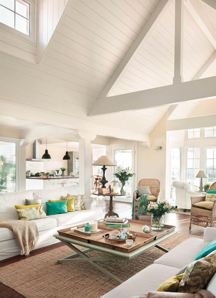 Salón con techo a dos aguas revestido de madera blanca_385011
