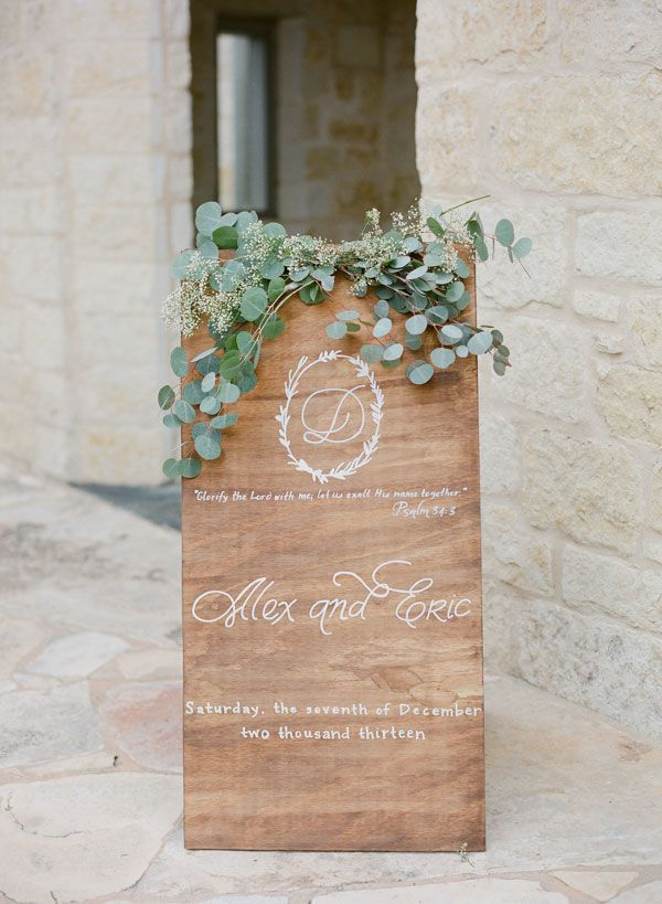 "Give your wedding signage an extra bit of enhancement by covering the tops with a bit of eucalyptus ""ivy"" and other small greenery."