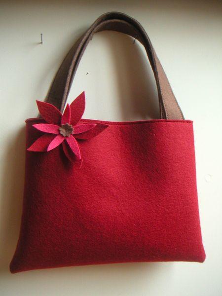 Petit sac en feutre de laine rouge . Anses marron. Fleur découpée et appliquée main rouge, rose et marron. Pièce unique. Cousu par mes soins...