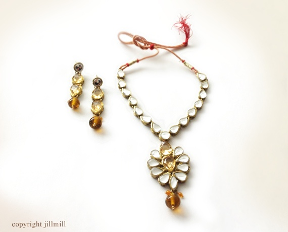 Single row of teardrop white kundans and a bold pendant with golden stones and beads.