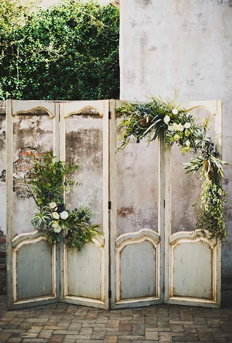A vintage ceremony altar with an antique folding screen dressed with white blooms and wild greenery | Brides.com