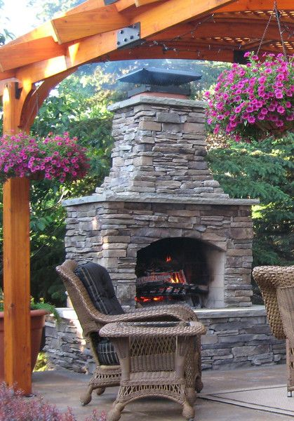 outdoor fireplace at the end of the patio covering. good placement.