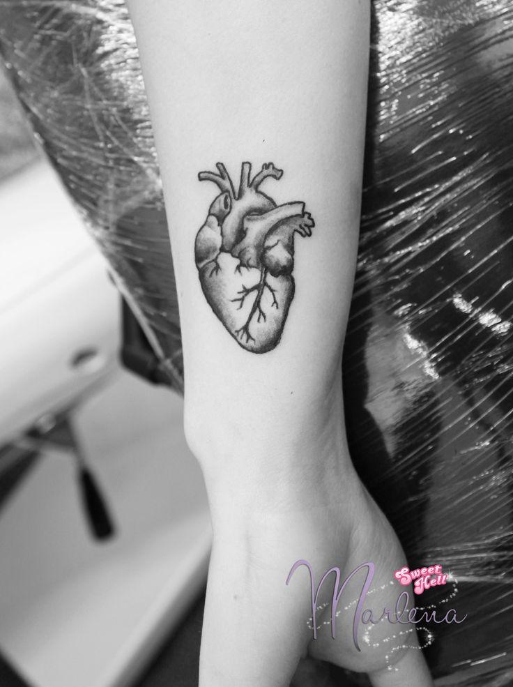 Minimal black human heart tattoo on a wrist. Black line styled, decorative little tattoo.