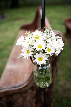 Pews at outdoor ceremony with daisies