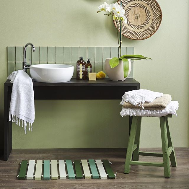 The clean lines and a restrained palette give this eco-green bathroom an elegant feel. A muted green wall in Resene Coriander and a streamlined vanity stained in Resene Colorwood Black Pepper set the mood for this inspiring bathroom, while the handmade element comes through in the slatted bathmat (Resene Scaramanga, Resene Secrets, Resene Coriander and Resene Seaweed) and stool (Resene Paddock). If you love this bathroom mat stay tuned for this #Reseneweekendproject Styling Claudia Kozub…