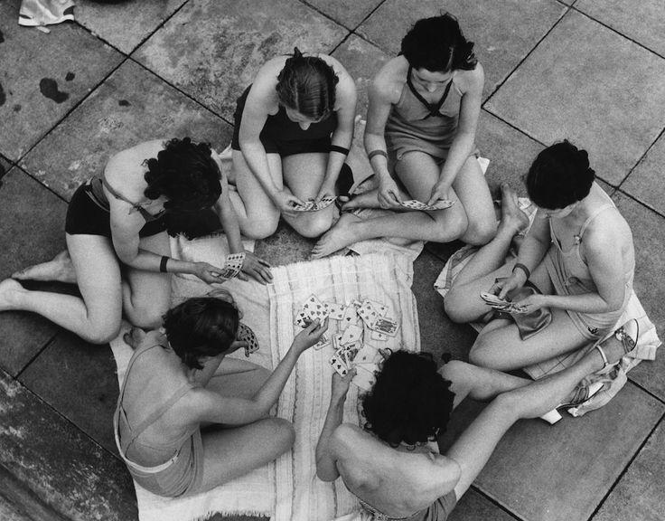 Ragazze in costume da bagno giocano a carte vicino alle piscine a cielo aperto a Hornsey, un quartiere settentrionale di Londra, 12 giugno 1937. (William Vanderson/Fox Photos/Getty Images)