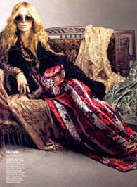 Furniture: wicker and tapestry  Throws: velvets  Attire: black cape boldly calms the busy skirt while the large beaded necklace stands out to compliment the skirt  Hair: layers  Makeup: natural...the mystique is in the oversized shades