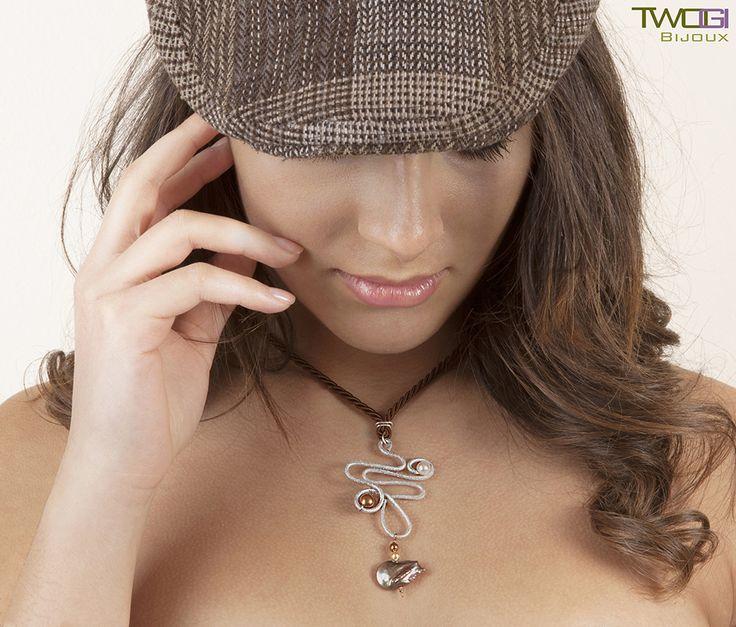 Collana con ciondolo in alluminio diamantato con perle Swarovski di colore bianco e golden,perla di fiume barocca color bronzo. Cordoncino marrone con cursore.