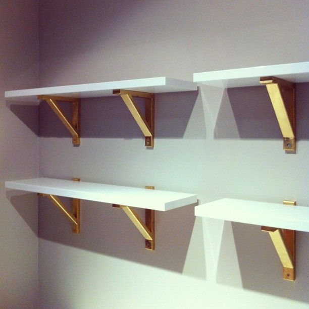 For the office - IKEA Hack: Ikea's glossy white shelves paired with their  wooden brackets, painted with Rust-oleum in metallic gold. Great hack via