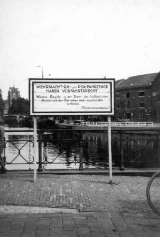 Bord waarop in de Duitse taal is aangegeven dat voertuigen van het leger, Rode Kruis en de politie voorrang hebben, met op de achtergrond de Oldehove te Leeuwarden. (tresoar.nl)
