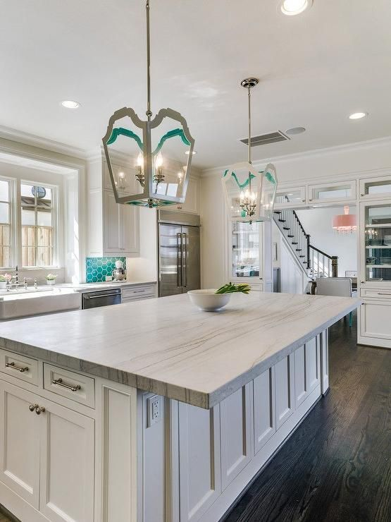 White and teal contemporary kitchen is illuminated by gray and teal lanterns hung over a white center island accented with nickel hardware and a White Macaubas Quartzite countertop.