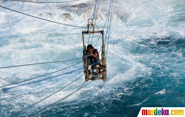 Nelayan menantang maut menyeberangi laut di tengah ombak besar menggunakan kereta gantung untuk menangkap lobster.