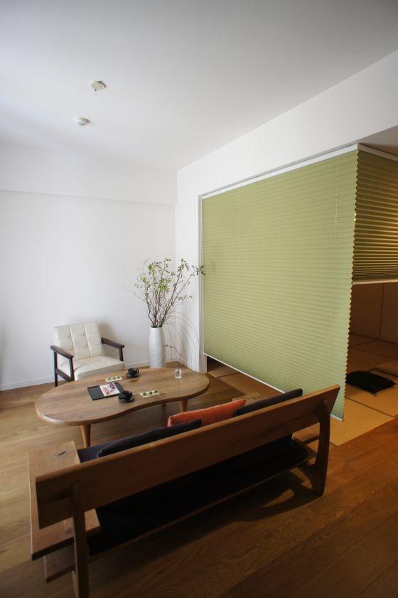 LDに続く和室の使い方。 分譲マンションに多いLDに続いて和室がある部屋のリノベーション。 「小さい子供がいるので畳スペースは使い勝手がいい。でも暮らしはちょっとステキにしたい。」 そんな要望をお持ちの方は多いのではないだろうか。 無垢フローリングと畳で分かれた二部屋をプリーツスクリーンで仕切り、和モダンの家具で合わせる。 ちょっとした工夫で部屋は大きく変わる。