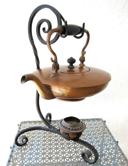 Old world charm in this antique copper tea kettle on a wrought iron stand.