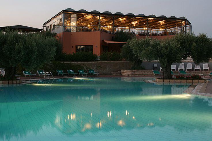 Villaggio Club Porto Rhoca ****  PISCINA: Situata tra ulivi secolari ed ampi spazi destinati alle attività sportive, è attrezzata con ombrelloni e lettini/sdraio, che sono a completa disposizione dei clienti che potranno godersi la vacanza nel meraviglioso panorama in totale relax!  ☀ Per info: ☎ (+39) 0662287376 ✉ info@ithotelsgroup.com