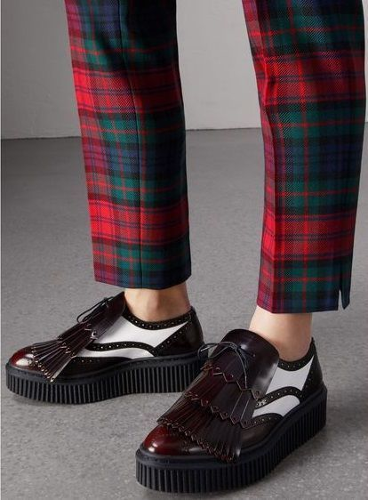 A pair of two-tone lace-up leather shoes, referencing creeper styles, revised with broguing and a tiered kiltie fringing. The Italian-made design is cut from glossy smooth leather, set on an accentuated tread and accented with contrast-coloured stitching.