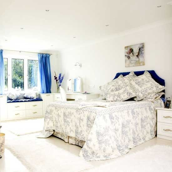 White bedroom with blue headboard and toile de joy bedlinen