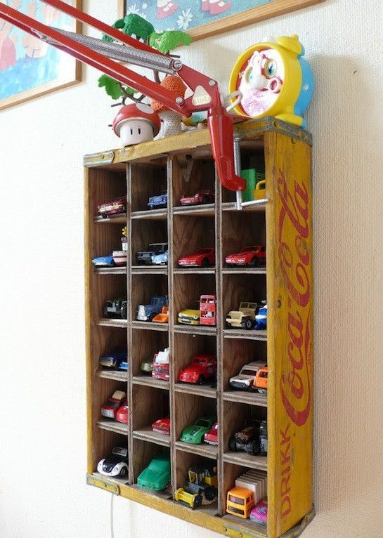 Old Coca Cola crate makes the perfect display case for matchbox cars in a vintage car room.