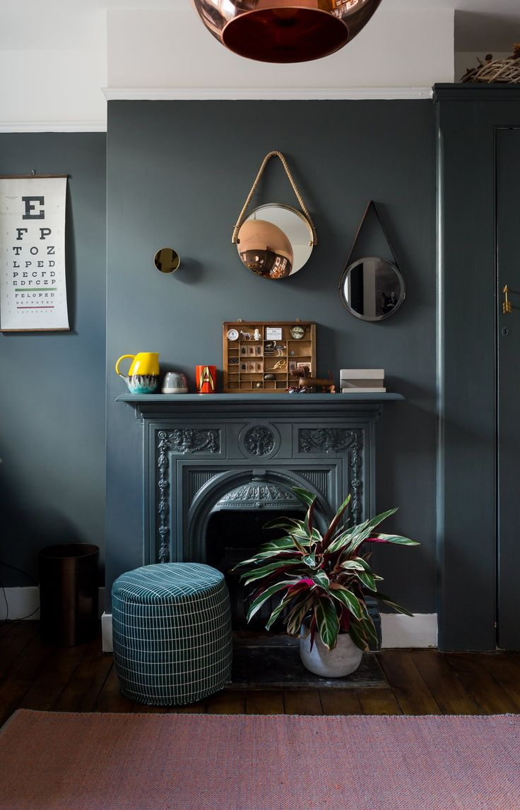Painting the fire surround and built-in cupboards in the same color as the walls has created a coherent look. The green pouf is Oyoy from Scandinavian Design Centre .