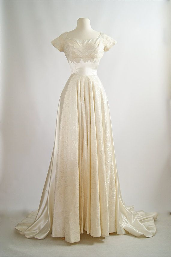 This is a stunning wedding gown by Cahill that was made in the 1950s! Consisting of satin and lace, this gown has a nice weight to it. It is fully