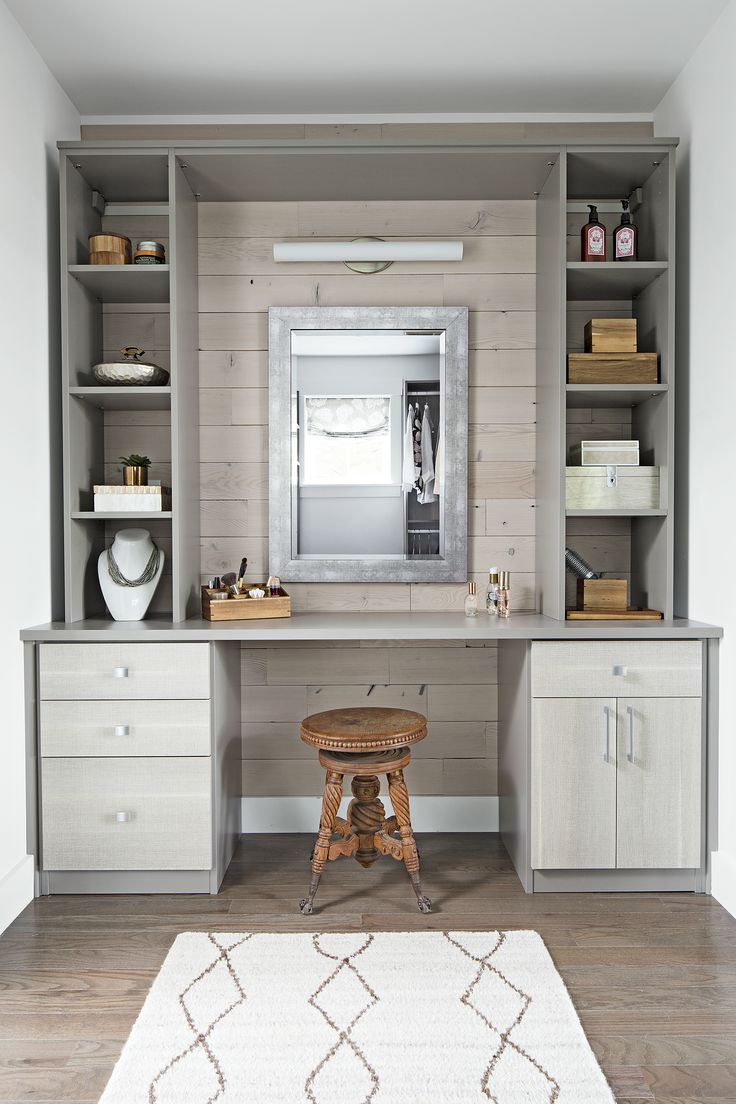 An accent wall of stained and distressed wafer-thin reclaimed-fir planks adds a slightly rustic touch to the grooming station in the master suite's dressing closet. Built-ins hold accessories; a vintage stool lends a one-of-a-kind accent.  Built-in: Classic Line in Cashmere Gray with Textured Pietra door fronts from California Closet's Tesoro Collection by Staci Foley, California Closets, 740-270-1115.  Rug: Zama hand-knotted rug; Dash & Albert  Accent wall: Minimalist Fir; Stikwood  ...