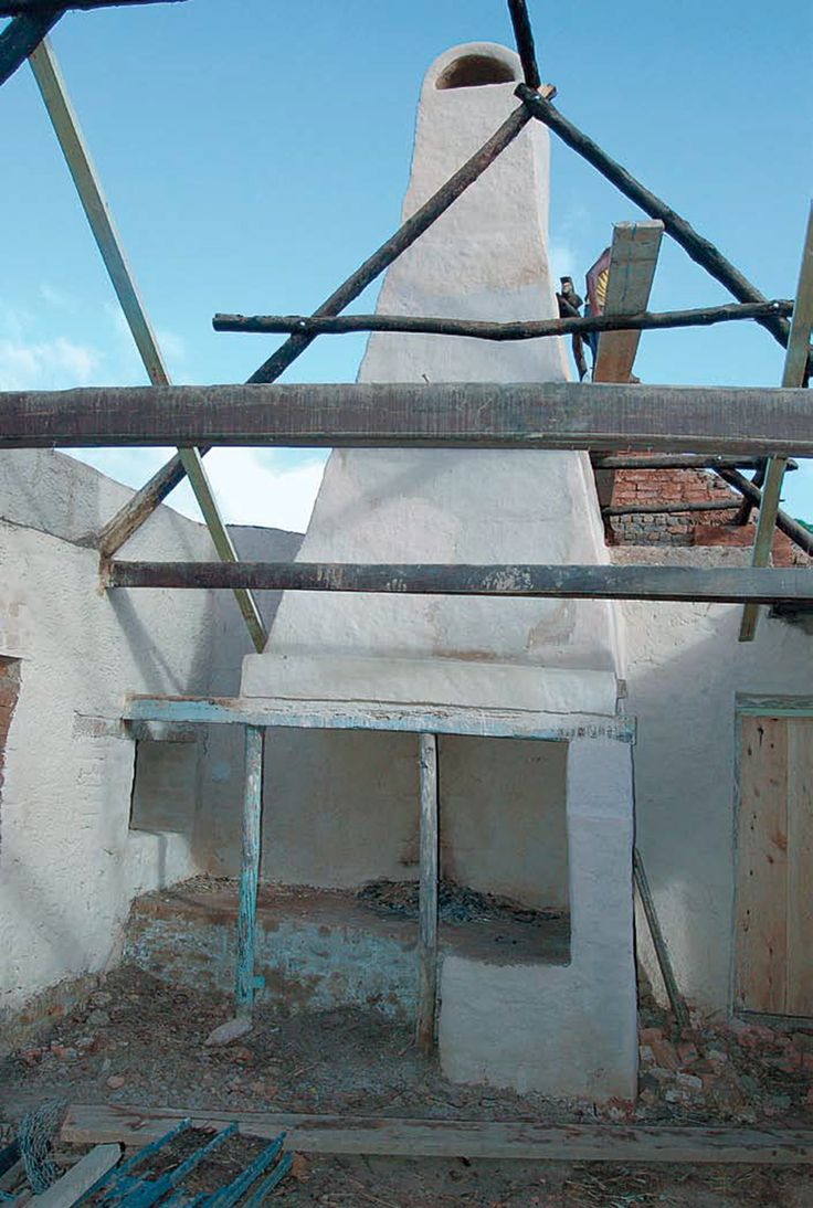 The hearth and chimney beigh rebuilt.  The roof trusses do not rest on top of the walls, but on beams set about half a metre lower down – this reduces the pressure exerted on the clay walls