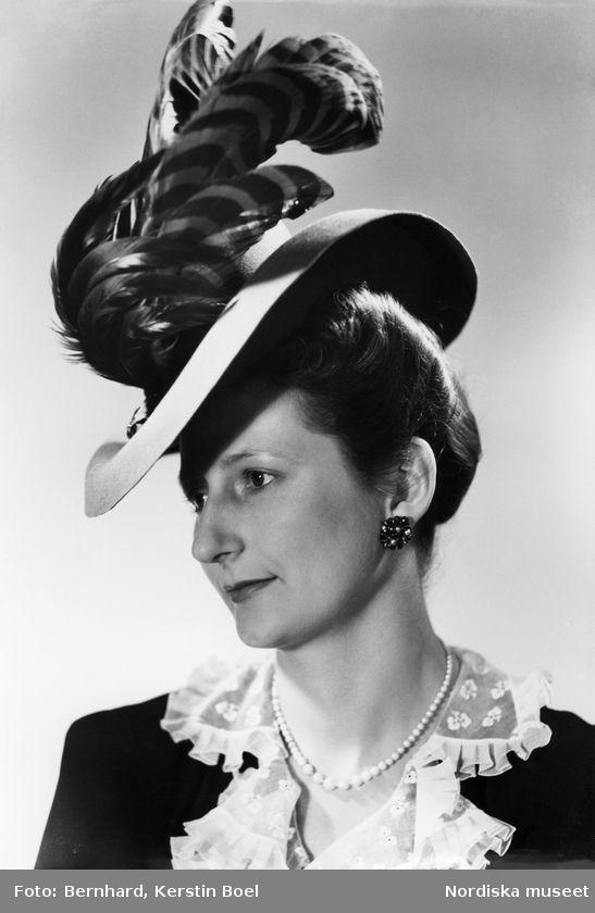 Modell i filthatt med plymer, vit spetskrage, vitt halsband, mörk jacka och örhänge. Foto: Kerstin Bernhard, 1950