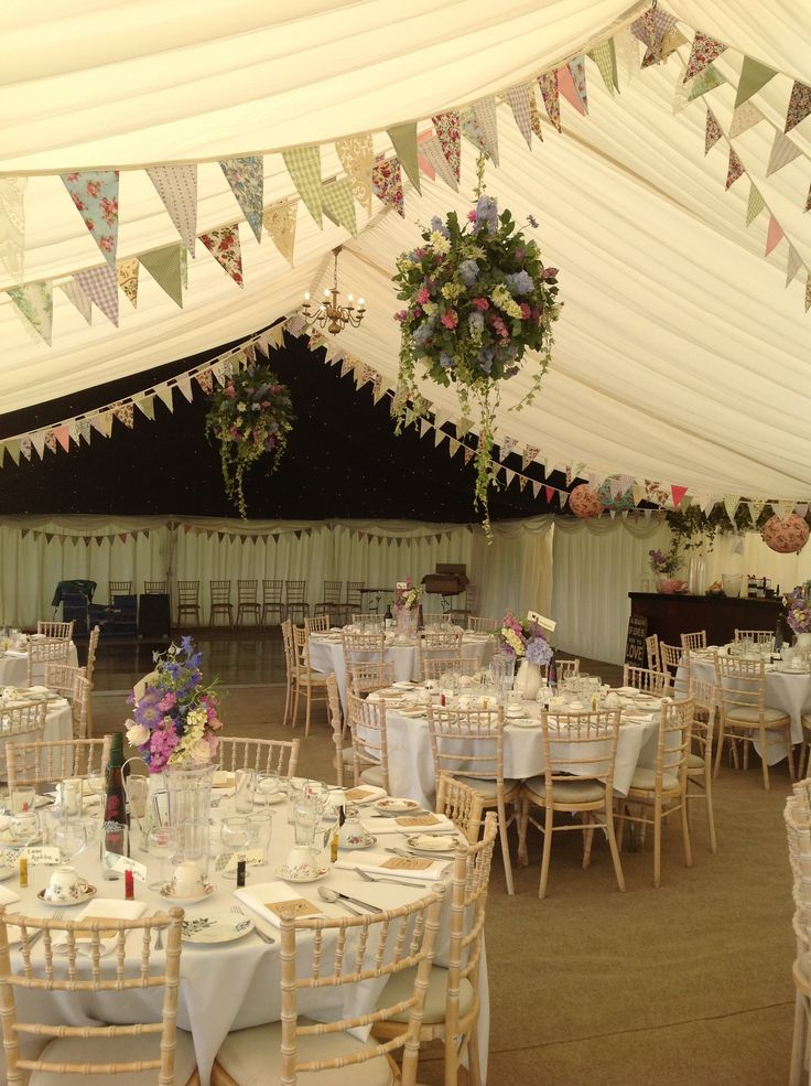Stunning hanging flower displays create the wow factor in this summer wedding marquee