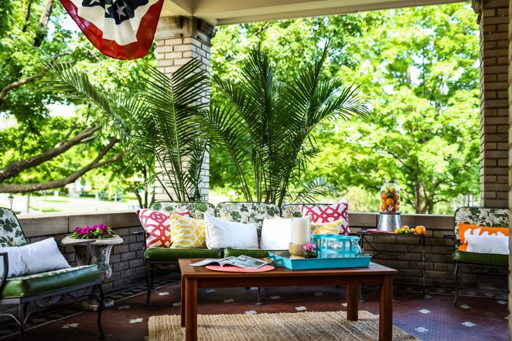 The updated front porch at the Summit Avenue mansion, as seen on DIY Network's Rehab Addict. Nicole Curtis, uses a mix of old and new to stage the home. She updated the previous owners patio set with fresh throw pillows.