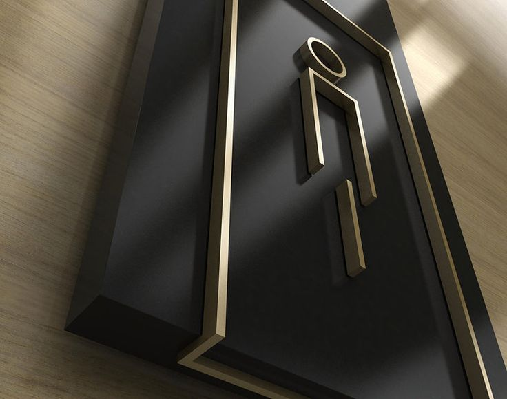 Detail view of an amenity sign in painted acrylic and brushed brass.
