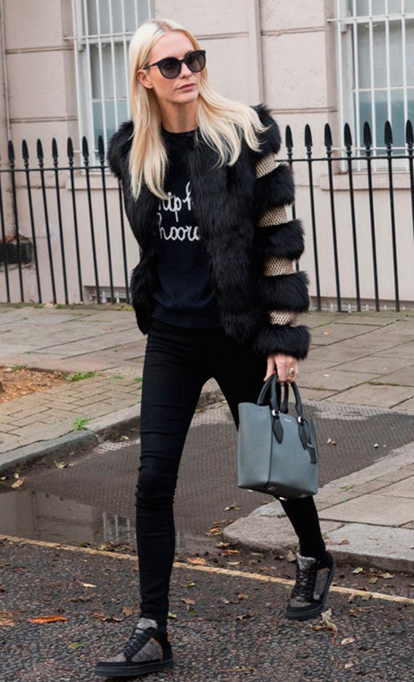 Poppy Delevigne posa para foto de street style usando tricot preto, casaco de pelo preto, calça skinny preta, tênis de cano alto e bolsa cinza