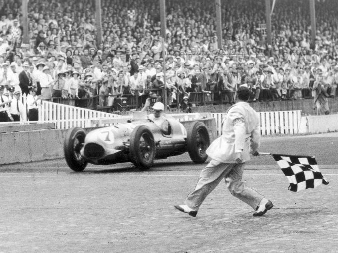 Waving his hand in a victory salute, Bill Holland flashes across the finish line in his Blue Crown Special to rack up a new record for the Indianapolis 500. Signaling the victory with the traditional checkered flag is Bill Vanderwater, assistant chief starter. May 31, 1949