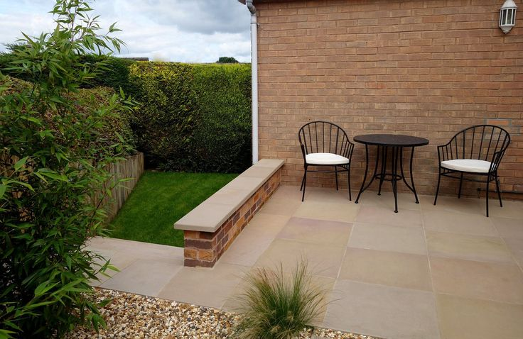 After Redesign & Landscaping - patio & top of steps leading to lower area - sawn sandstone patio paving & wall coping, grasses, bamboo, contemporary garden, low maintenance garden