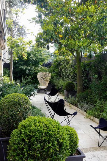 A garden in Montmartre, Paris. love the black butterfly chairs.