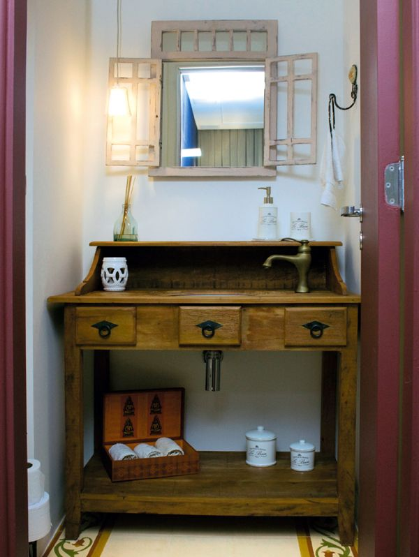 """Lavabo da arquiteta Juliana Harrison, de 2,8 m², mistura seu lado rústico com um vintage cheio de estilo. Desde o piso de ladrilho hidráulico até o espelho em formato de janela – de madeira patinada –, o espaço reúne detalhes encantadores. """"A intenção era trazer um pouco do aconchego do campo para esse ambiente, por isso a escolha de elementos como a bancada no estilo de escrivaninha, feita de madeira de demolição"""", detalha a profissional."""
