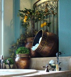 A wrought iron wall grill and bronze pots storing towels and greenery give this bathroom an old world appeal.