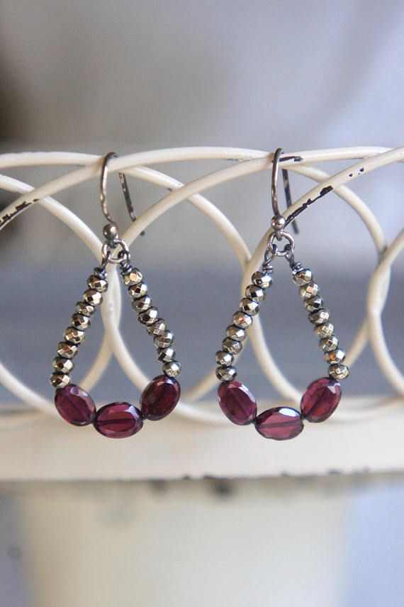 Beautiful garnet gemstone earrings. Faceted, oval garnet gemstone beads are hand wired and hang between faceted hematite gem beads. Sterling silver ear wires finish off the pair. All handmade and one of a kind. Length: 1 from bottom of ear wires. Please be sure to read my shop