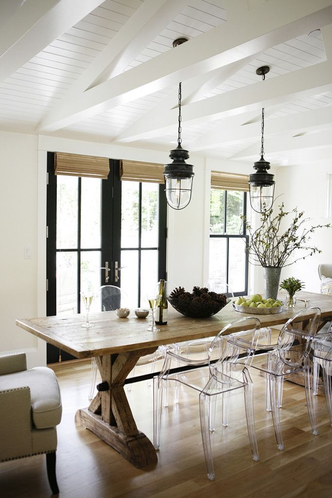 Modern farmhouse dining room with oak table and lucite chairs. I'm also loving the beamed, vaulted ceiling and black steel-frame french doors.